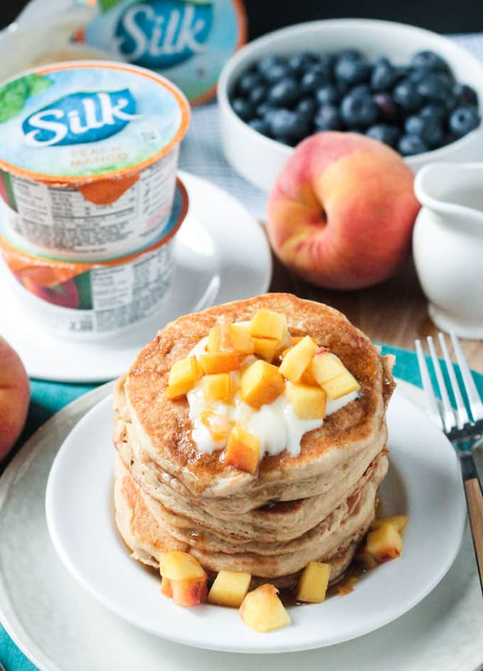 Peach pancakes topped with diced peaches and yogurt cups in the background.