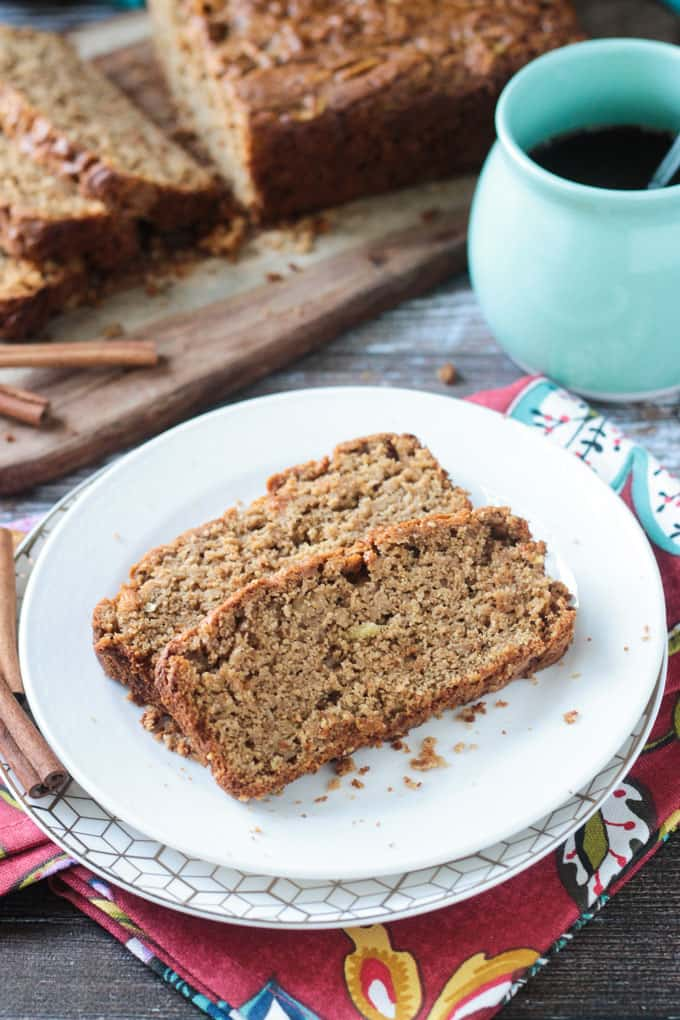 Two slices of apple cinnamon bread on a white plate. Blue cup of coffee and the rest of the loaf of bread in the background.
