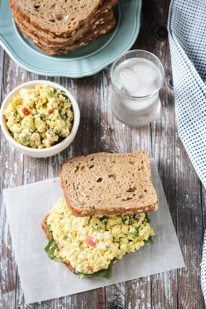 Curried tofu salad on whole grain bread with glass of water behind.