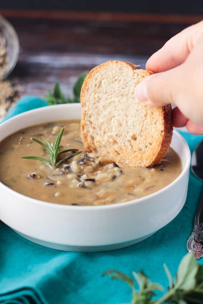 Slice of toasted baguette being dipped into a bowl of wild rice soup.