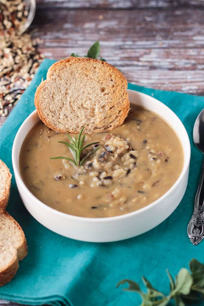 Wild rice soup in a white bowl with a sprig of rosemary and a slice of baguette.