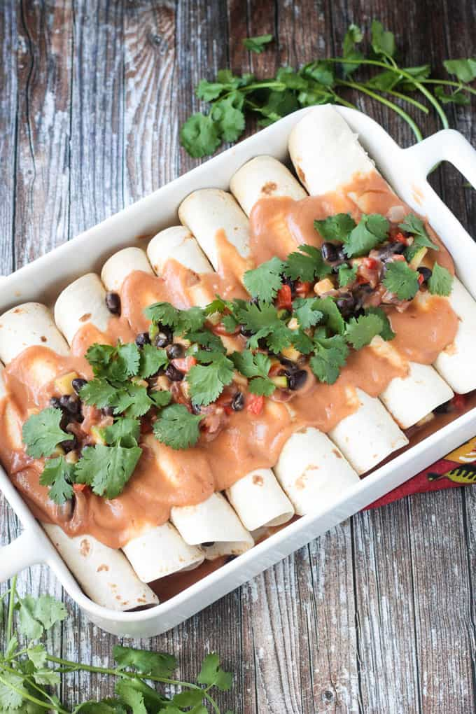 Pan of enchiladas topped with salsa and lots of cilantro.