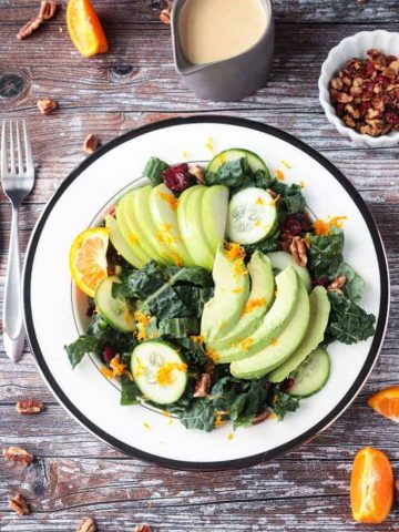 Overhead view of a kale salad with apples, avocados, cucumbers, and orange zest.