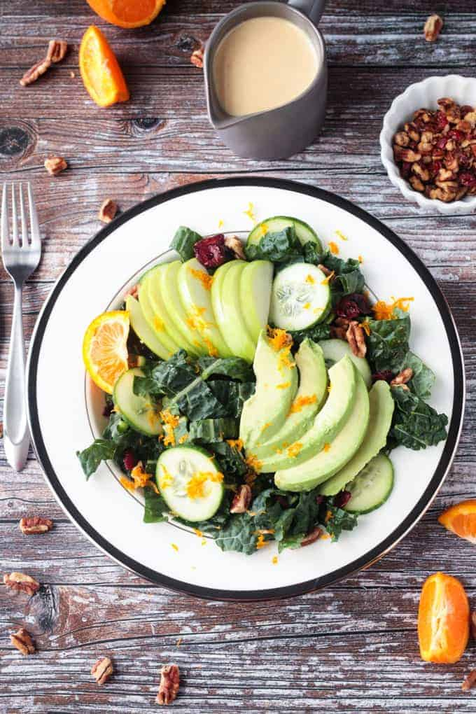 Lacinato kale superfood salad w/ apple slices, avoacdo slices, cucumber slices, and orange zest sprinkled on top.