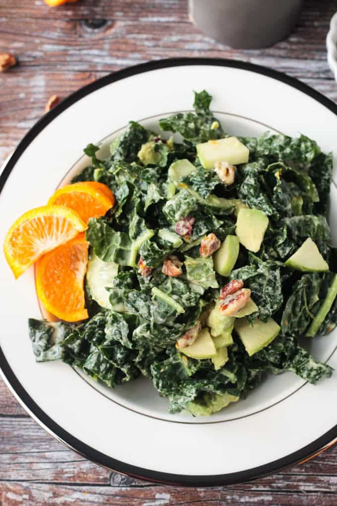 Bowl of kale salad with avocado, apples, pecans, and three orange slices on the side.