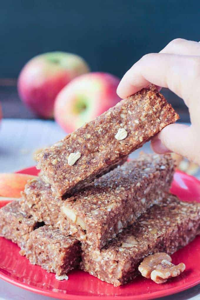 Hand grabbing an apple pie bar from a stack of more bars. Two apples in the background.