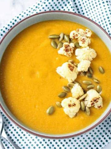 Bowl of sweet potato cauliflower soup on a blue/white dotted kitchen towel.
