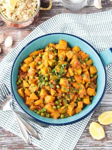 Bombay Potatoes and Peas in a blue skillet. Small dish or rice in the background.