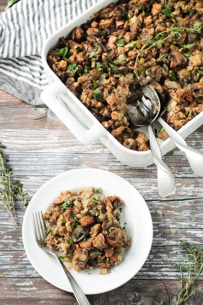 Small plate of vegan stuffing in front of a baking dish full of stuffing.