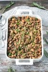 Pan of vegan stuffing with mushrooms, celery, and lots of herbs. A gray and white striped kitchen towel lies nearby along with a serving fork and spoon.