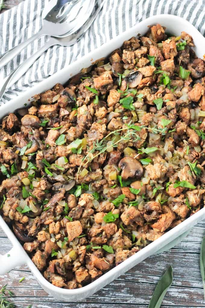 Pan of vegan stuffing with mushrooms. Fresh thyme sprigs lie on top.