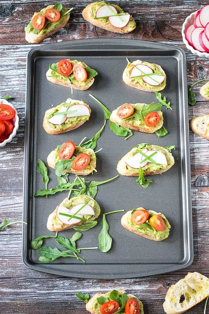 Baking sheet of vegan bruschetta appetizers.