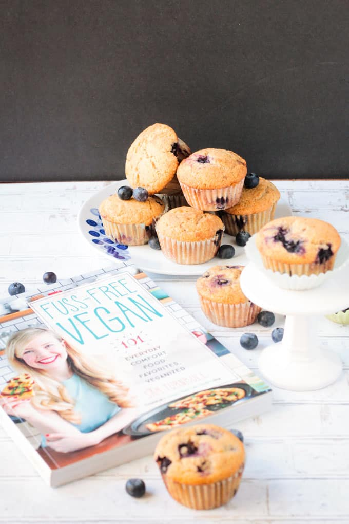 Fuss-Free Vegan Cookbook next to a plate of blueberry muffins