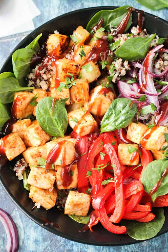 Overhead close up of baked tofu cubes and red pepper strips in a bowl drizzled with bbq sauce.