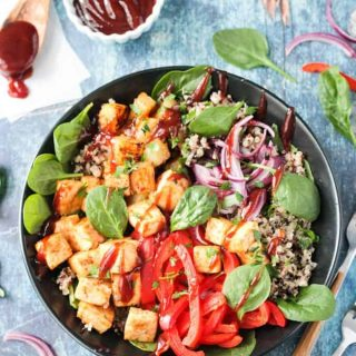 Overhead view of a BBQ Hawaiian Tofu Bowl w/ peppers, onions, pineapple, spinach, quinoa, and a drizzle of bbq sauce.