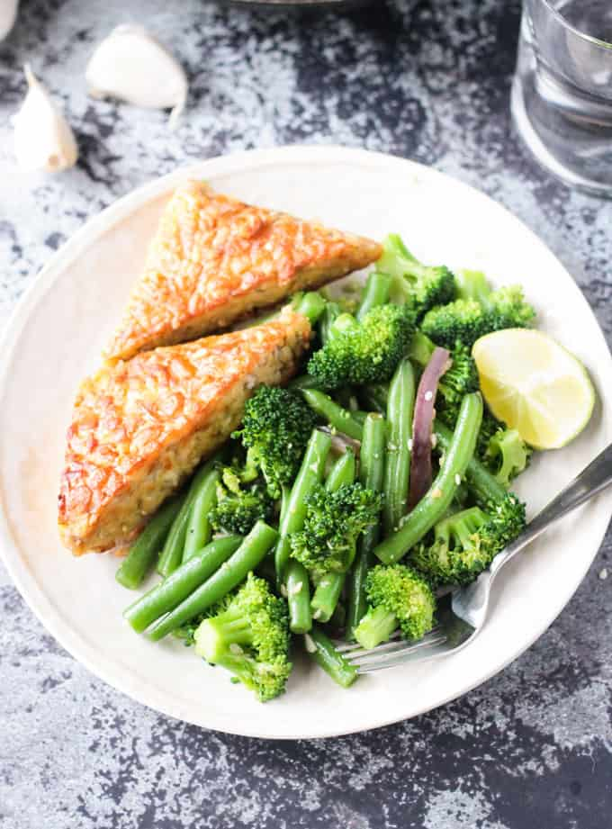 White plate with green bean broccoli stir fry with two slices of tempeh, a lemon wedge, and a fork resting on the side.