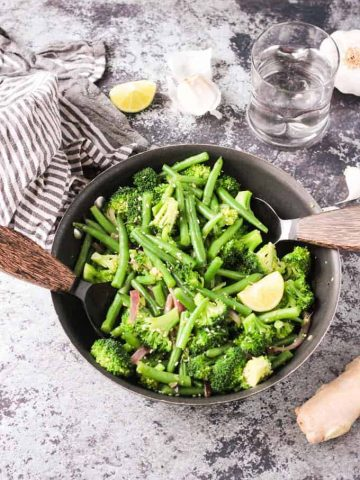 Two wooden handled serving spoons in either side of a skillet with green bean broccoli stir fry. Gray and white striped dish towel, lemon wedges, and garlic slices nearby.