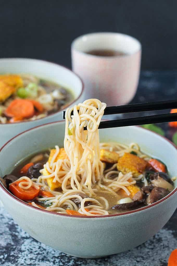 Chopsticks holding up a bite of noodles from a bowl of ramen soup.
