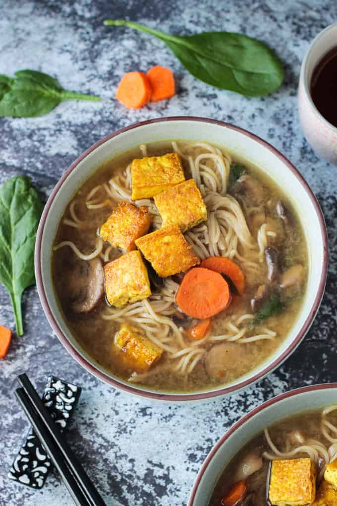 Overhead view of a bowl of mushroom ramen soup with carrots, spinach, and topped with crispy tofu.
