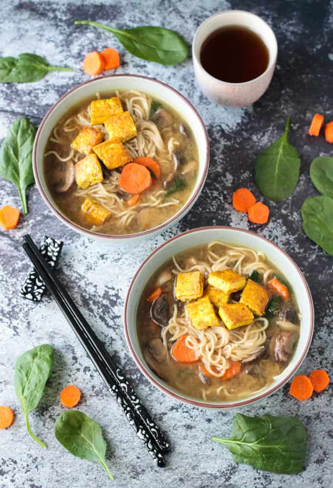 Two bowl of mushroom ramen soup. Black chopsticks on the table next to the soup bowls. Fresh spinach and sliced raw carrots scattered around the bowls.