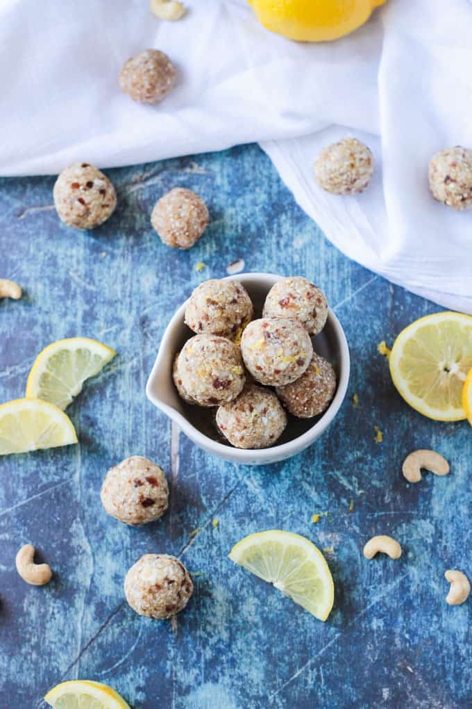 A bowl of lemon date balls on a blue background. Raw cashews, lemon wedges, and more date ball scattered around the bowl.