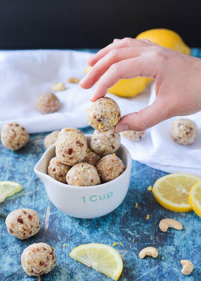 A hand picking up a lemon date ball from a bowl full of date balls.