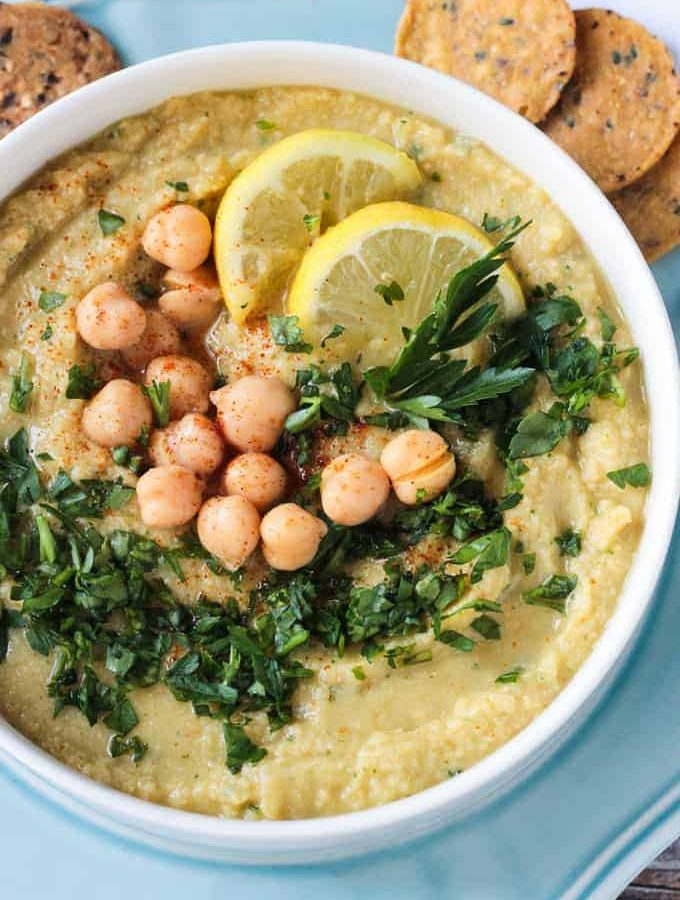 Bowl of Lemon Parsley Oil Free Hummus topped with chickpeas, chopped parsley, and lemon wedges.