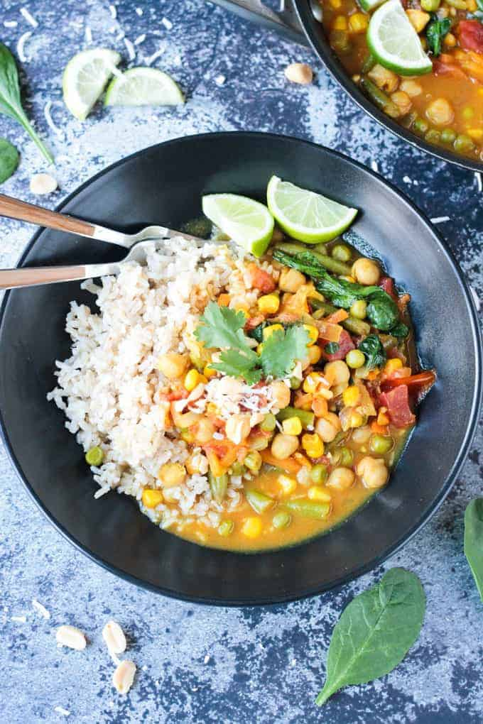 Sprig of cilantro on top of curry vegetables and rice.