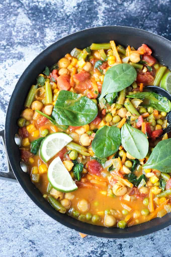 Overhead view of mixed vegetables in sauce topped with fresh spinach and lime wedges.
