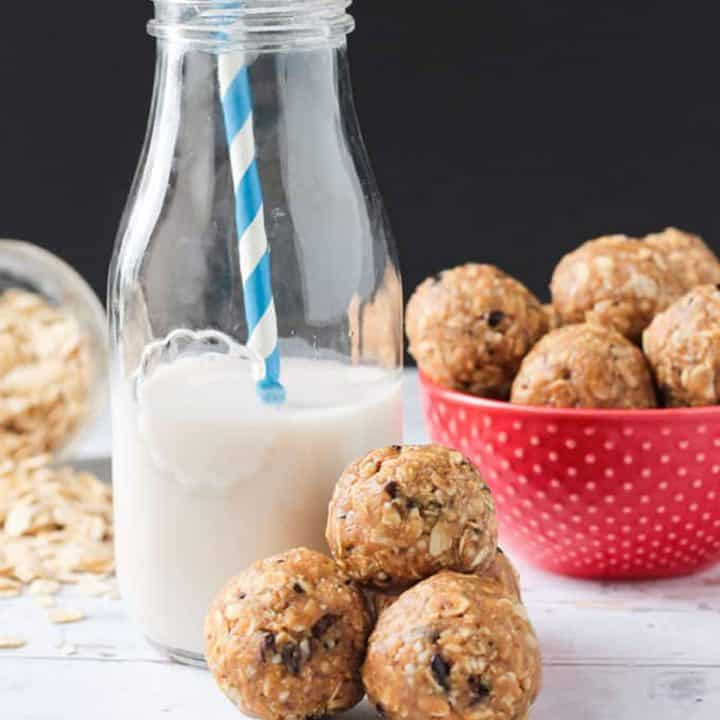 Three oatmeal peanut butter balls beside a glass of milk.