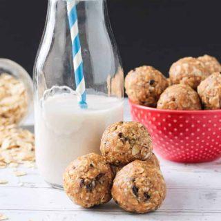 Three oatmeal peanut butter balls beside a glass of milk.