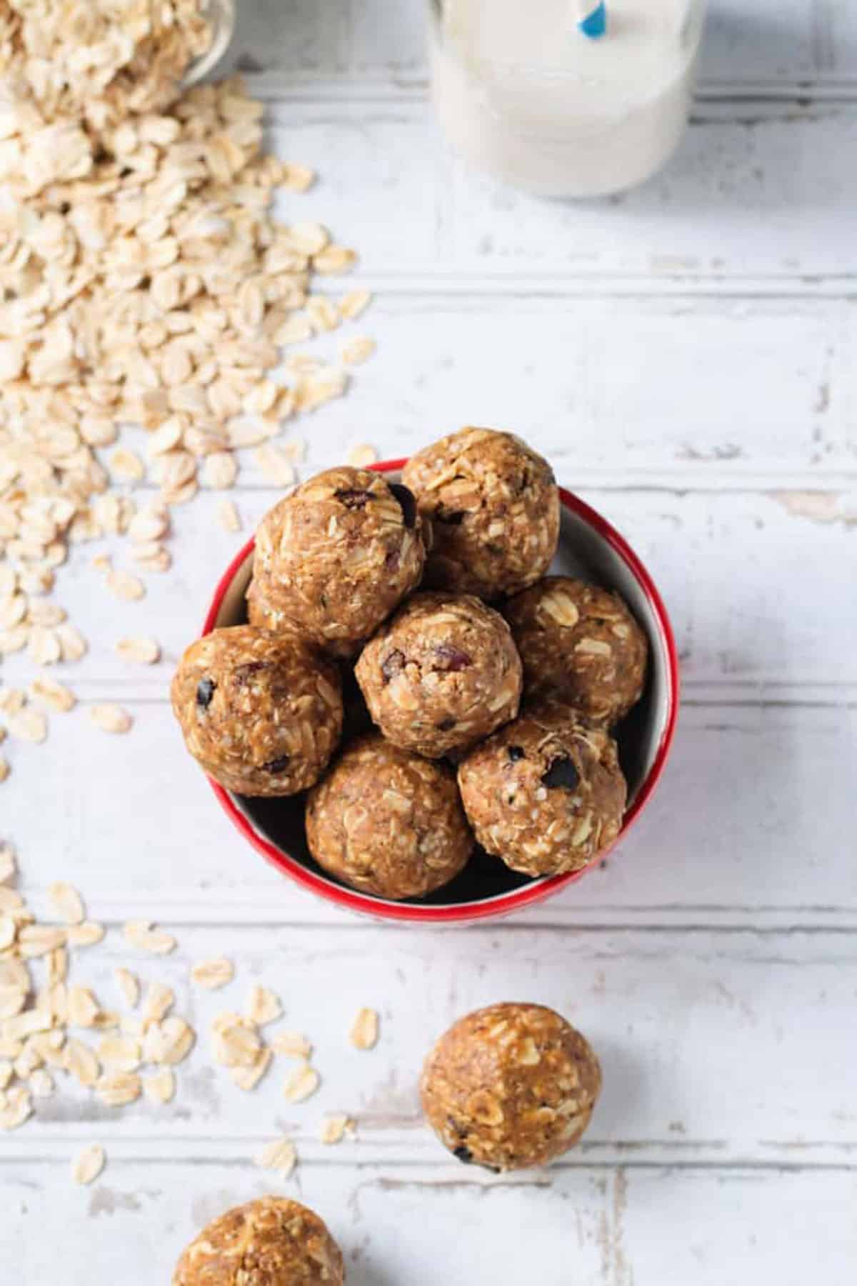Overhead view of a bowl of oatmeal peanut butte balls. Raw oats scattered around the bowl.