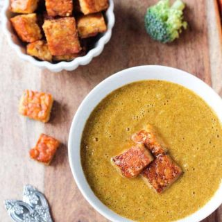 "Overhead view of a bowl of vegan broccoli soup topped with three tempeh ""croutons."" More croutons and a fresh broccoli floret lie nearby."