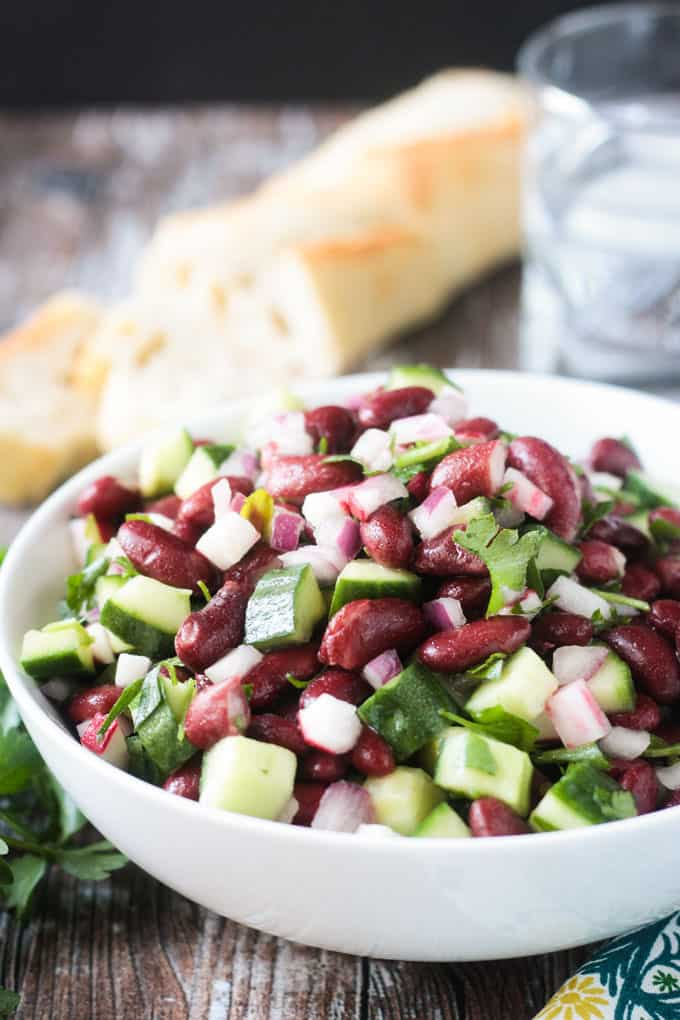 Close up front view of a white bowl of kidney bean salad.