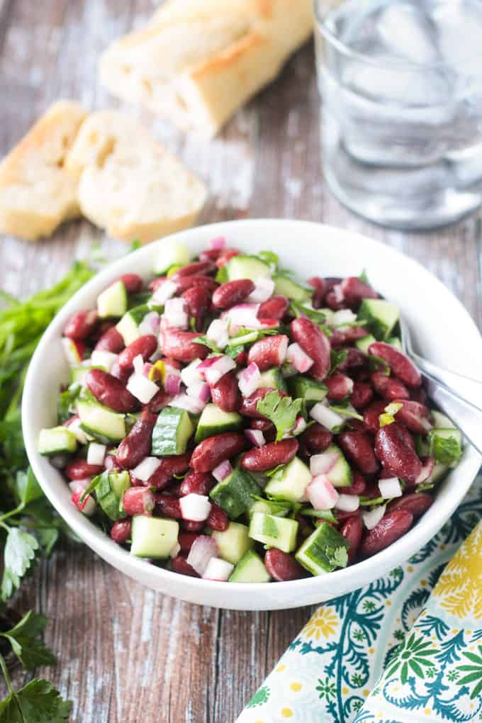 Kidney bean salad in a white bowl with cucumbers, red onion, radishes, and fresh parsley.