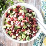 Bowl of kidney bean salad with cucumbers, radishes, red onion, and parsley.
