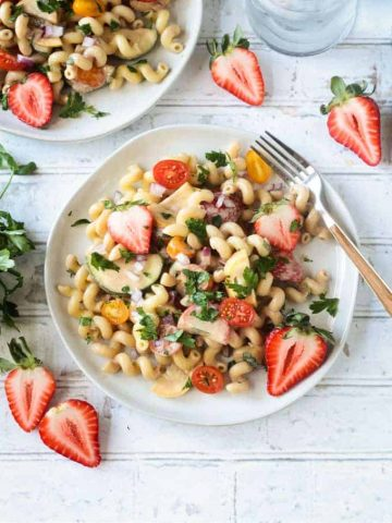 Summer pasta salad on a white plate on a wide wooden picnic table. Wooden handled fork on the side of the plate. Fresh halved strawberries on the table around the plate.