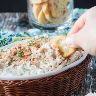 Hand dipping a baguette slice into a bowl of cold crab dip.