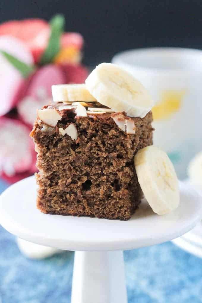 Square slice of banana bread cake toped with fresh banana slices and slivered almonds.