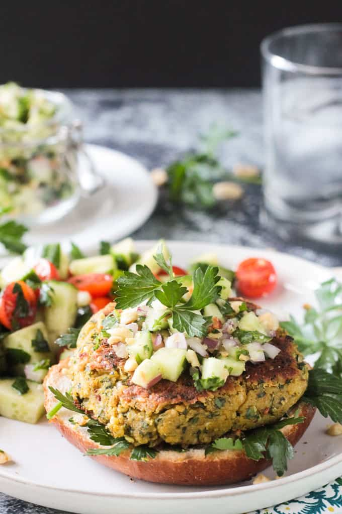 Open faced falafel burger topped with cucumber peanut relish and a sprig of parsley.
