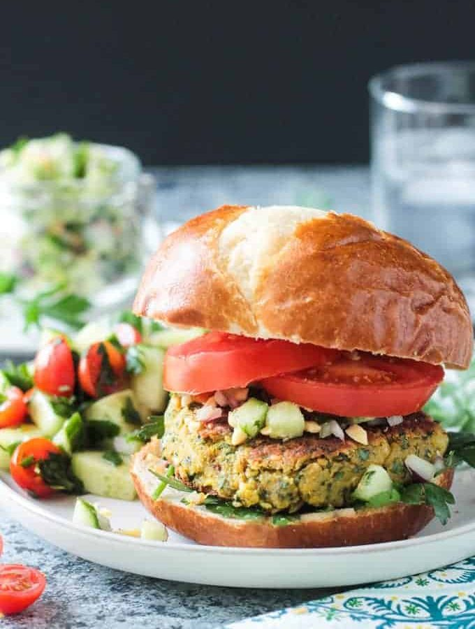 Front view of a falafel burger on a pretzel bun with sliced tomatoes and cucumber peanut relish.