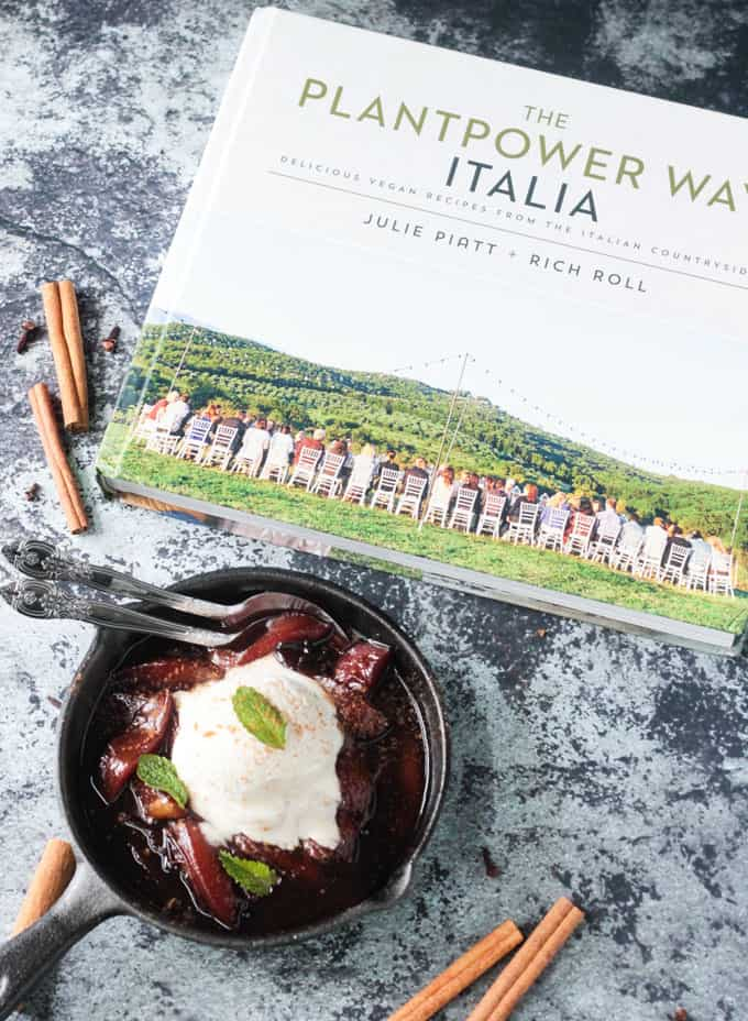 A skillet of poached nectarines next to The PlantPower Way: Italia Cookbook