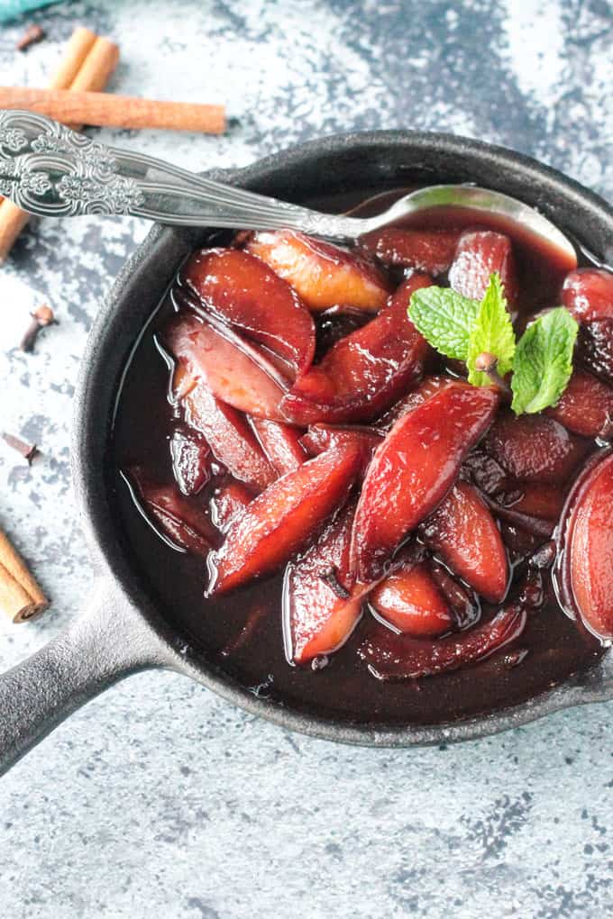 Two metal spoons in a cast iron skillet full of poached nectarines in red wine.