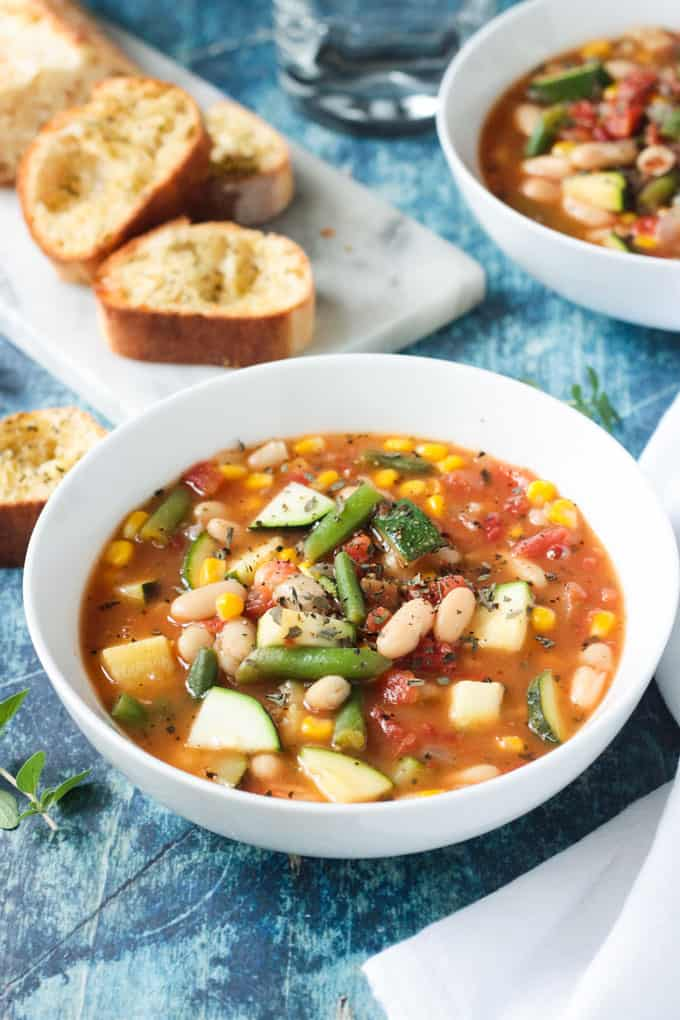 Close up of a white bean soup recipe with green beans, tomatoes, zucchini, and corn.