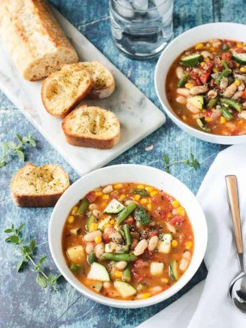 Loaf of sliced bread behind a bowl of summer white bean vegetable stew.