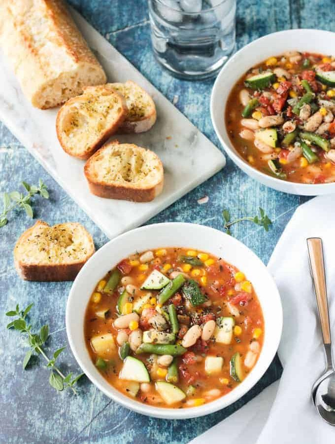 White Bean Soup recipe in a white bowl next to a white napkin with a wooden handled spoon. Loaf of sliced crunchy bread on the table behind next to another bowl of soup.