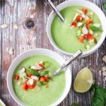 Two bowls of cold cucumber soup with silver metal spoons in them. A lime wedge lies nearby.