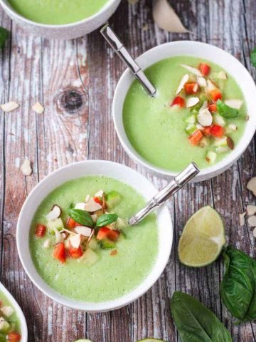 Two bowls of cold cucumber soup with silver metal spoons in them.