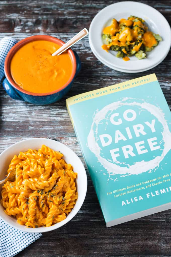 Go Dairy Free cookbook next to a bowl of mac and cheese and a bowl of vegan cheese sauce.