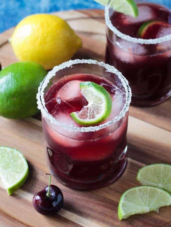 Closeup overhead view of a glass of Tart Cherry Sparkling Lemonade garnished with sugar on the rim and a twisted lime slice floating in the glass.